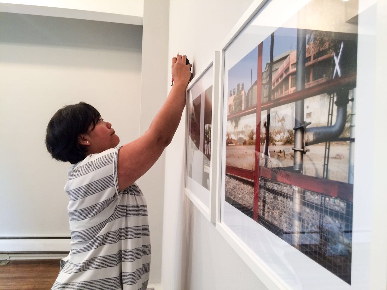 Intern hanging frames at Turner House, Penarth